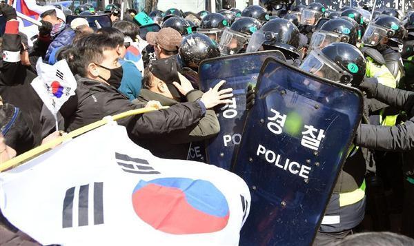 韓国憲法裁判所の罷免決定言い渡し後、機動隊と衝突する朴槿恵大統領の支持者ら=10日、ソウル(共同)