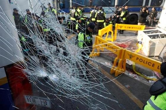 憲法裁の近くで負傷者が出た現場で、窓ガラスを割られたバス=10日、ソウル(ロイター)