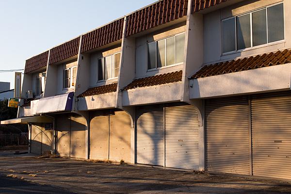 閉鎖した店の並びと西日