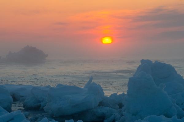 流氷と日の出かすみかかる