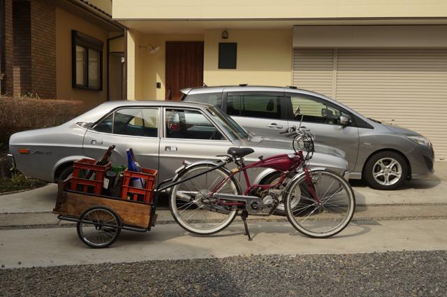 酒瓶を載せたリアカーを牽く原付・バタバタ自転車・モペッド