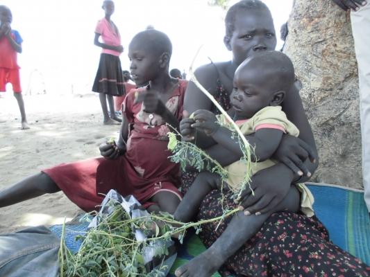 南スーダン、野生の豆を食べる子ども